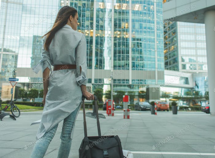 stylish woman with road bag in city