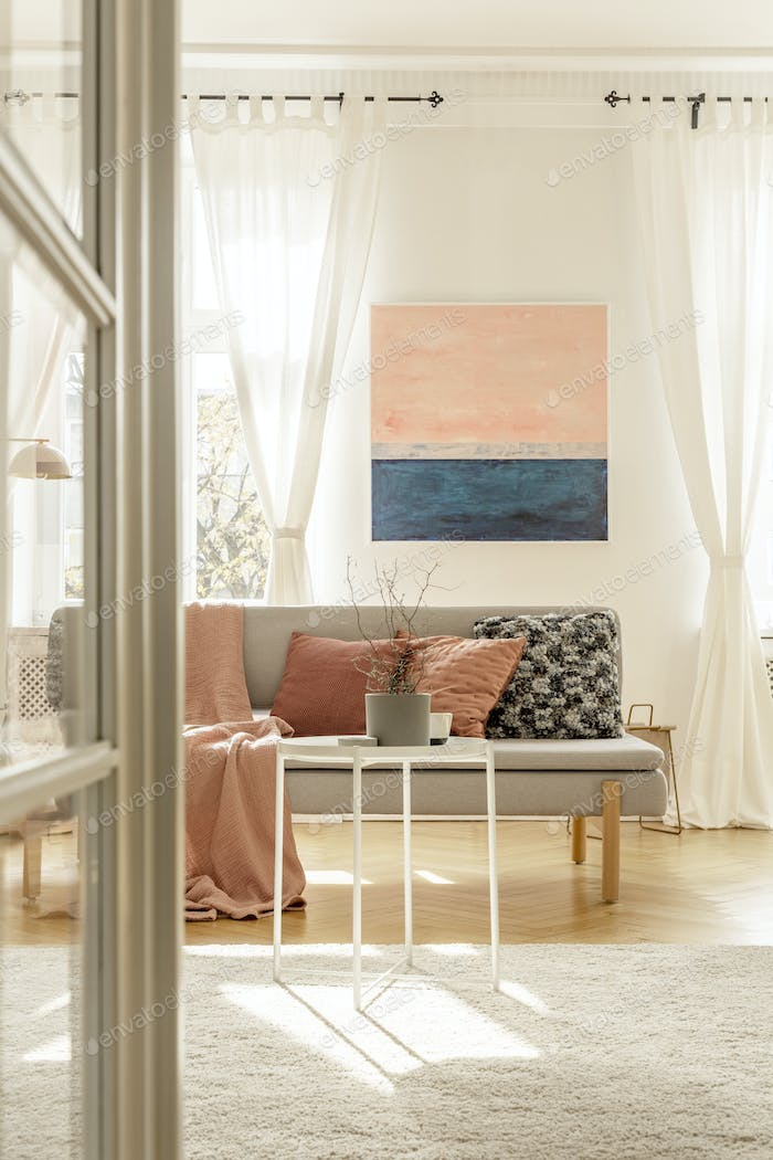 Pastel pink pillows and blanket on grey scandinavian sofa in elegant interior