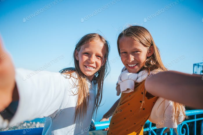 Little smiling girls in mountains take selfies