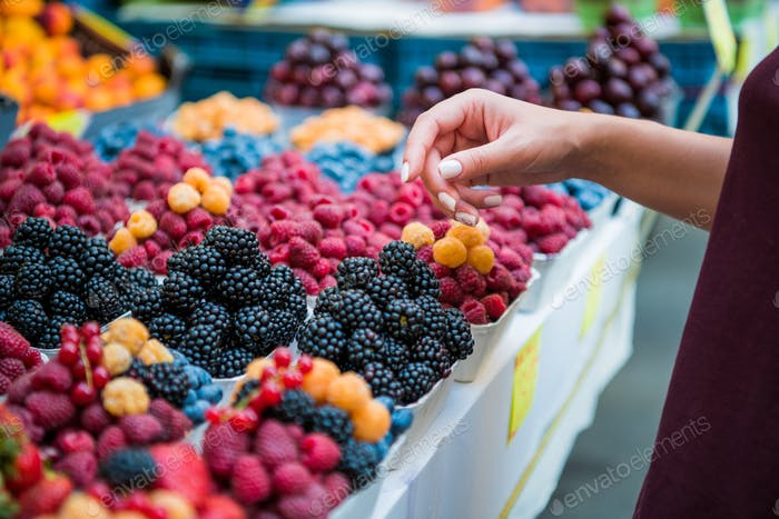 Marketplace with different fruits. Seller's hand on colorful berry background outdoors. Sale
