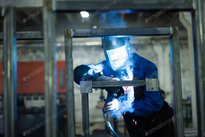 worker in protective gear, welding square pipes