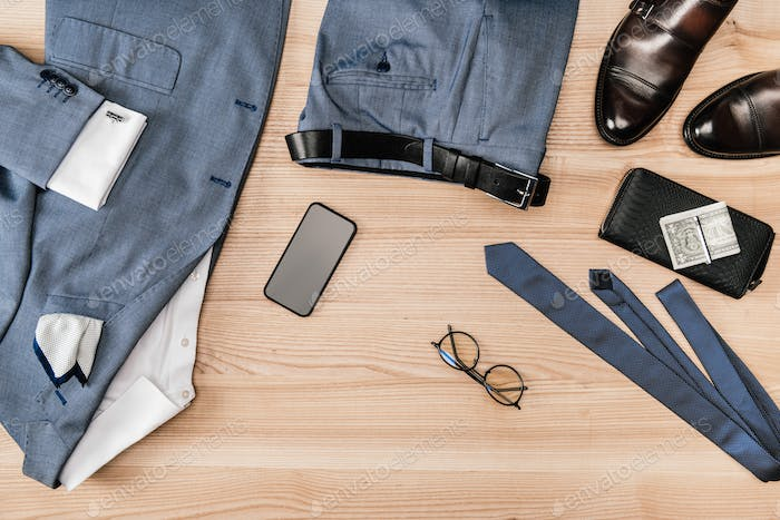 top view of suit and accessories with smartphone on wooden tabletop