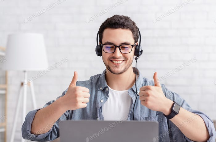 Online work. Smiling guy with headset shows sign excellent with hand