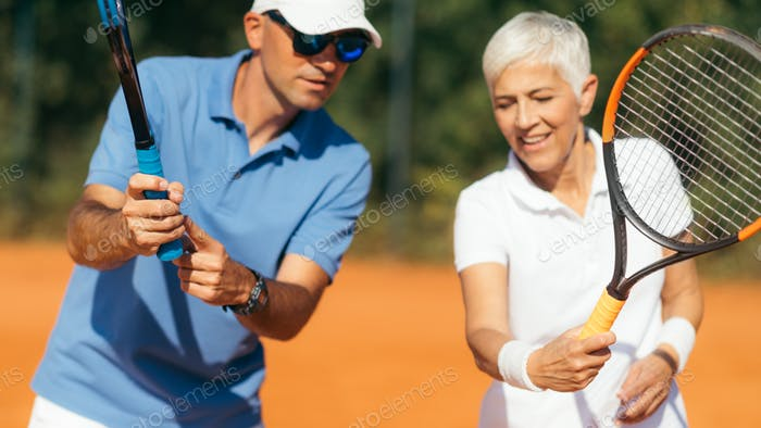 Tennis Instructor with Senior Woman