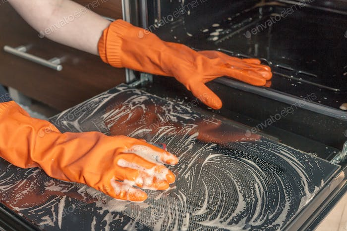Kitchen cleaning. Girl's hands in gloves wash clean the stove, kitchen oven in the kitchen