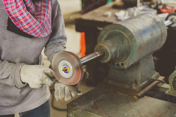 Closeup angle Grinder hand holding and Grinding the spare parts of metal gear