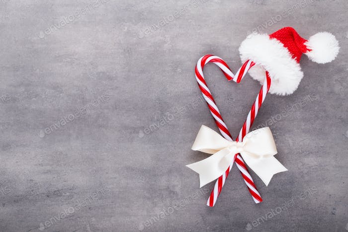 Christmas candy canes, stick and decor on color background.