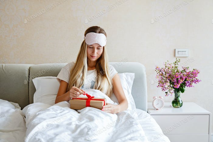Young Caucasian Woman With Blonde Hair And Blindfold Lying in Bed And Unboxing Present