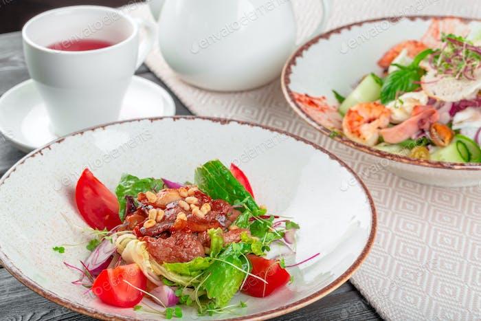 Closeup of a fresh green salad with sliced seared tenderloin steak