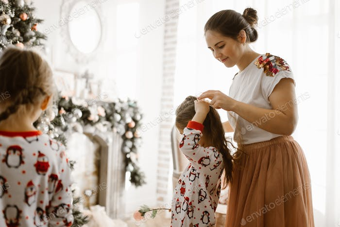 Beautiful mother braids her little daughter's braid in the light cozy room with wonderful New