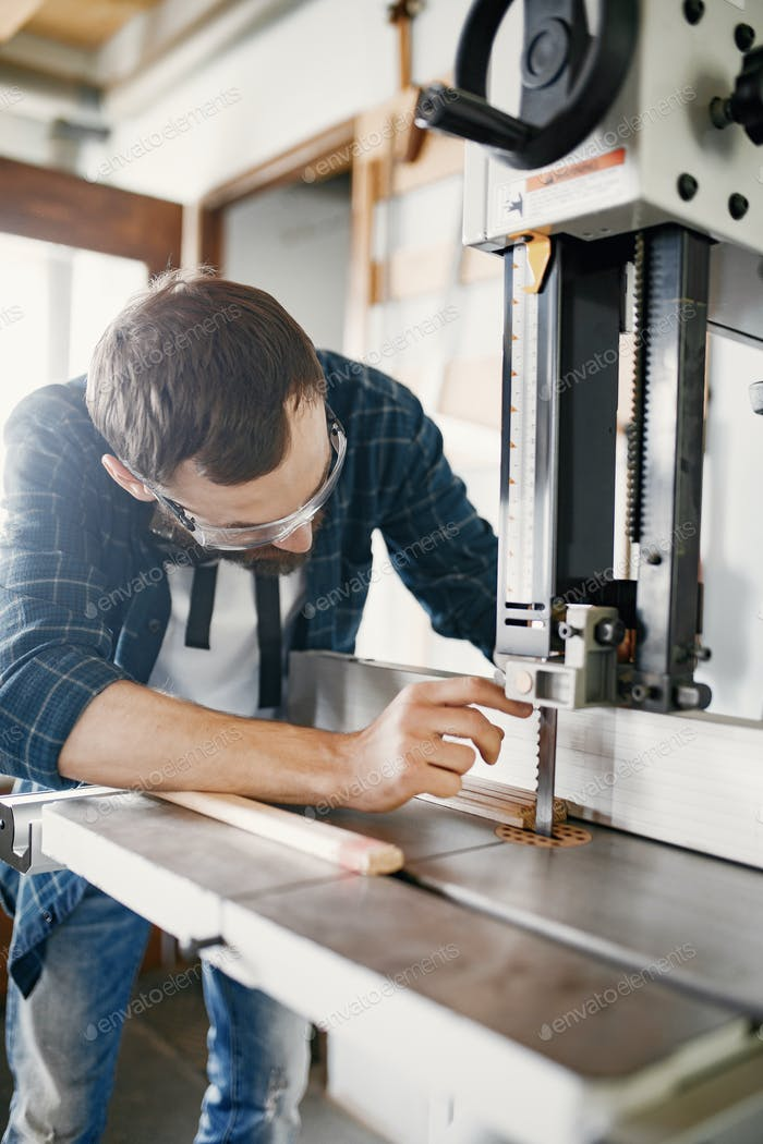 Профессиональный плотник, работающий с пильной машиной
