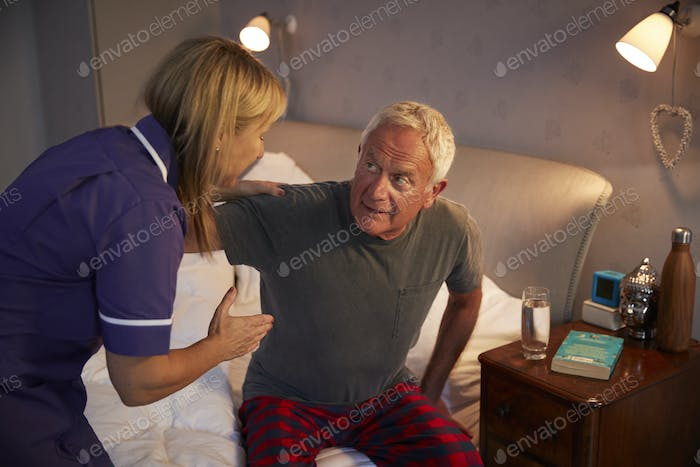 Nurse Helping Senior Man Out Of Bed On Home Visit