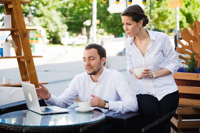 Happy business people on their lunch outside at the coffee shop