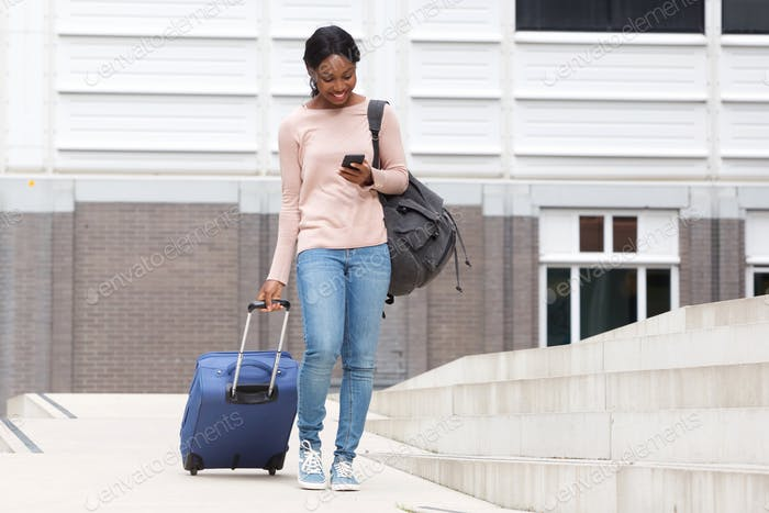 Full body happy young african american woman walking with suitcase bag and cellphone