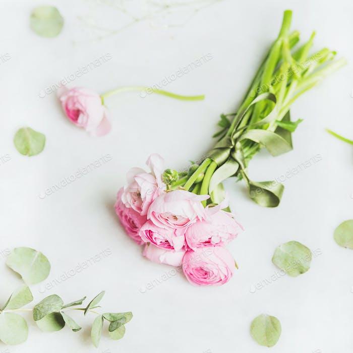 Light pink ranunkulus flowers on marble background