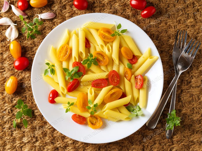 Penne pasta with yellow and red tomatoes decorated with basil on sisal mat background,
