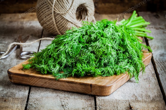 bunch of fresh organic dill on a cutting board with rope