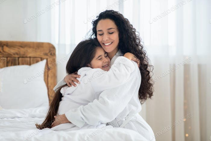 Liebevolle Mutter und Tochter in Bademänteln umarmen