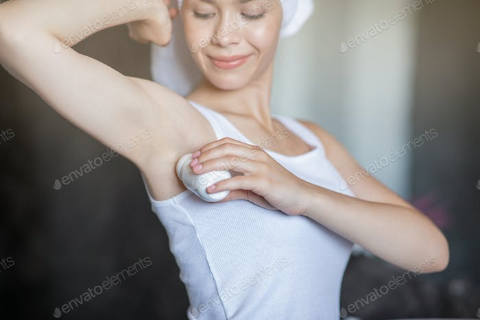 Lovely lady appying antiperspirant deodorant on her armpit indoors