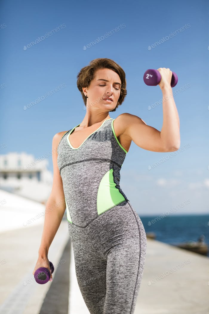 Pretty woman in gray sport suit doing exercises with dumbbells thoughtfully looking on the sea
