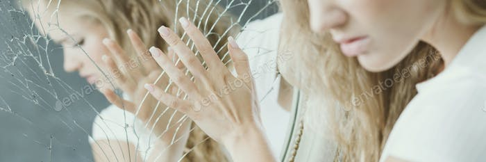 Girl touching broken mirror