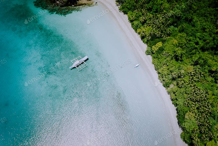 Aerial drone view of the beautiful paradise lagoon and white sand beach. Local boats on the surface