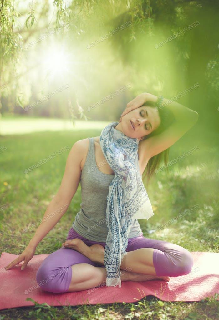 Ruhige und friedliche Frau üben achtsam Bewusstsein durch meditieren in der Natur mit Sonnenflamme.
