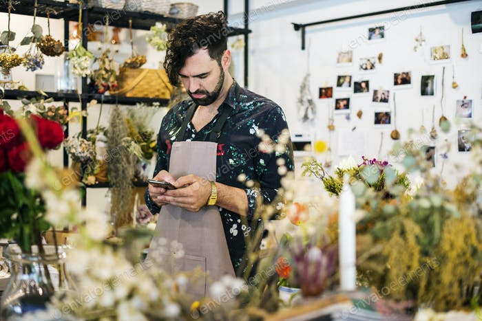 Bearded man using mobile phone in flower shop