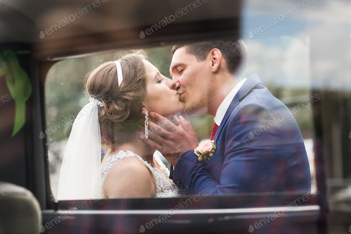 Beautiful Romantic Bride with Groom Kissing and Embracing Outdoors