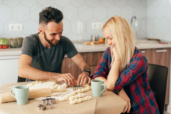 Young loving couple of boyfriend and girlfriend smiling prepare baked goods.