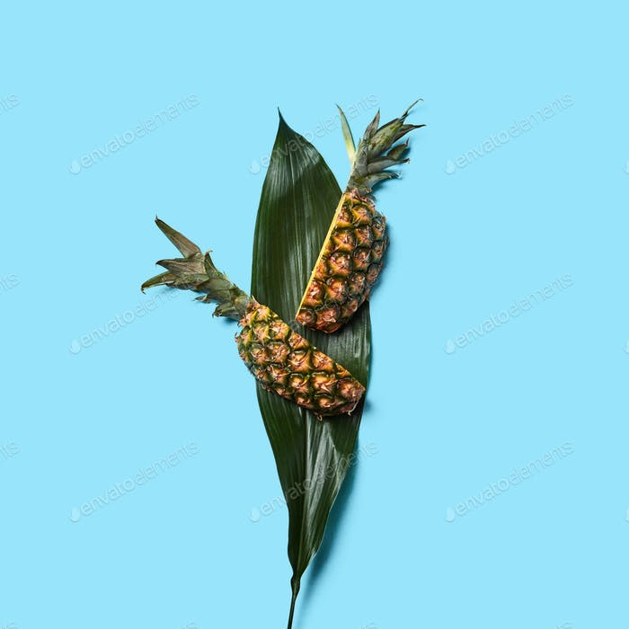 Green leaf and slices of ripe organic pineapple on a blue background with space for text. Flat lay