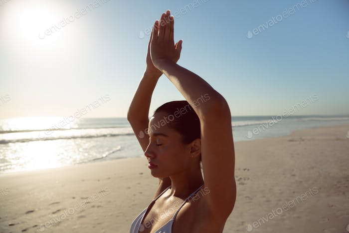 Beautiful woman performing yoga on the beach