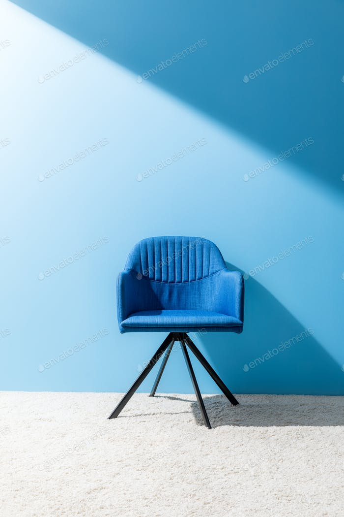 comfy blue chair in front of blue wall