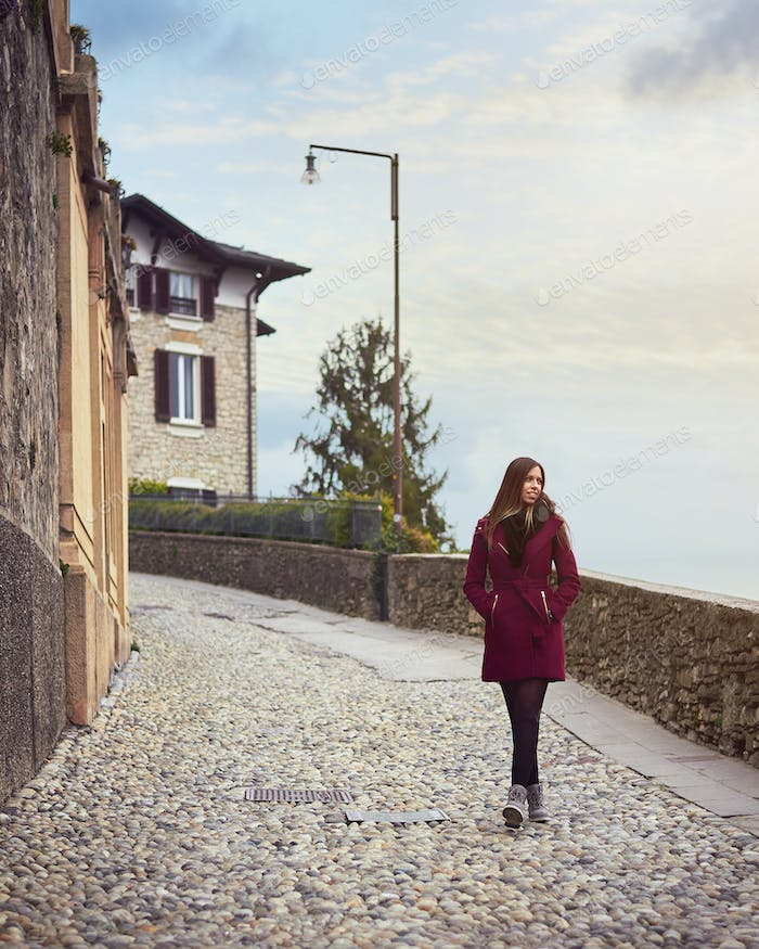 Young woman walking by a pedestrian street in italy