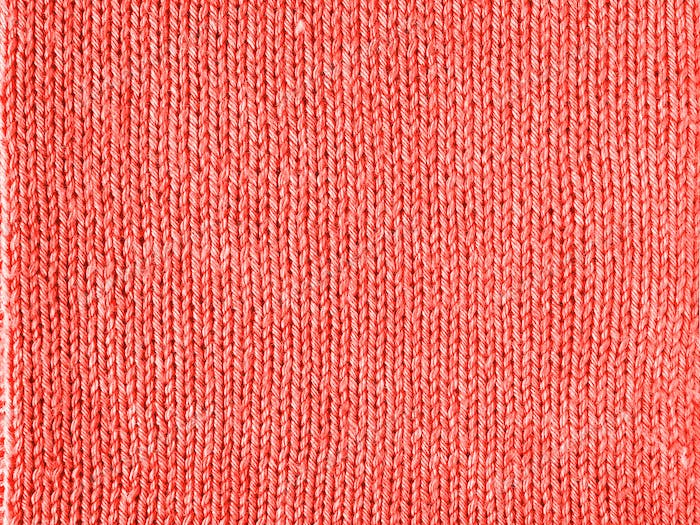 Knitted Living Coral texture jersey as background