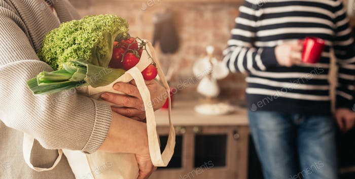 Eco Bag With Vegetables In Hands Of Unrecognizable Woman In Kitchen