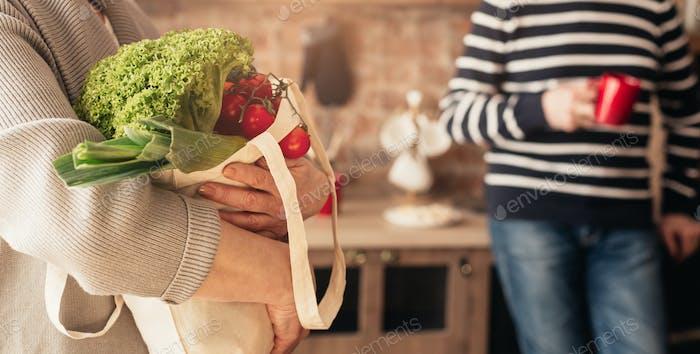 Eco bolsa con verduras en manos de irreconocible mujer en la cocina