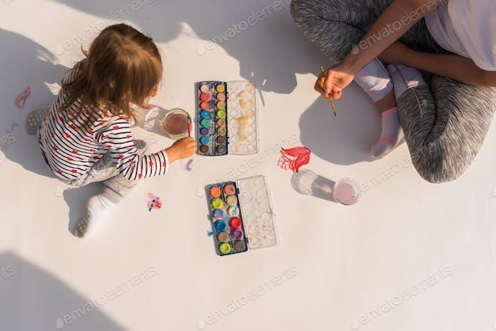 Kind mit Mutter malt mit Plakatfarbe im Freien auf dem Boden auf einem großen Blatt Papier.