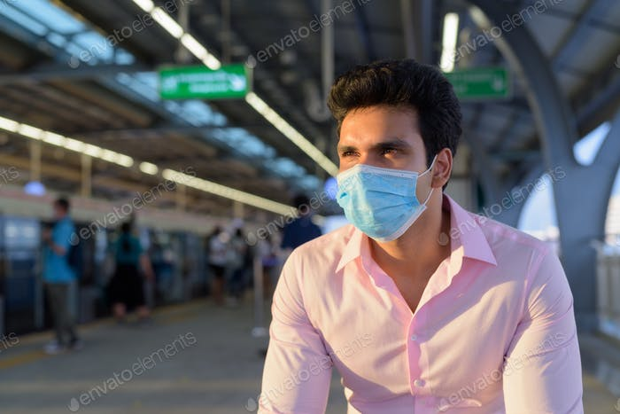 Young Indian businessman wearing mask and sitting with distance while waiting at the skytrain