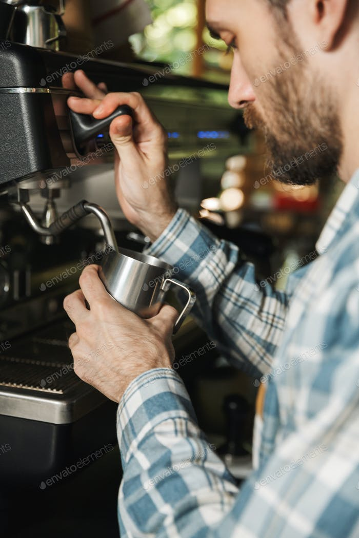 Image of focused barista man making coffee while working in cafe