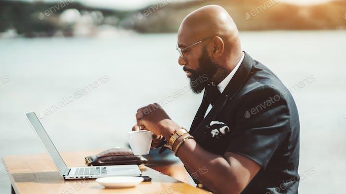 Black man with laptop in street bar
