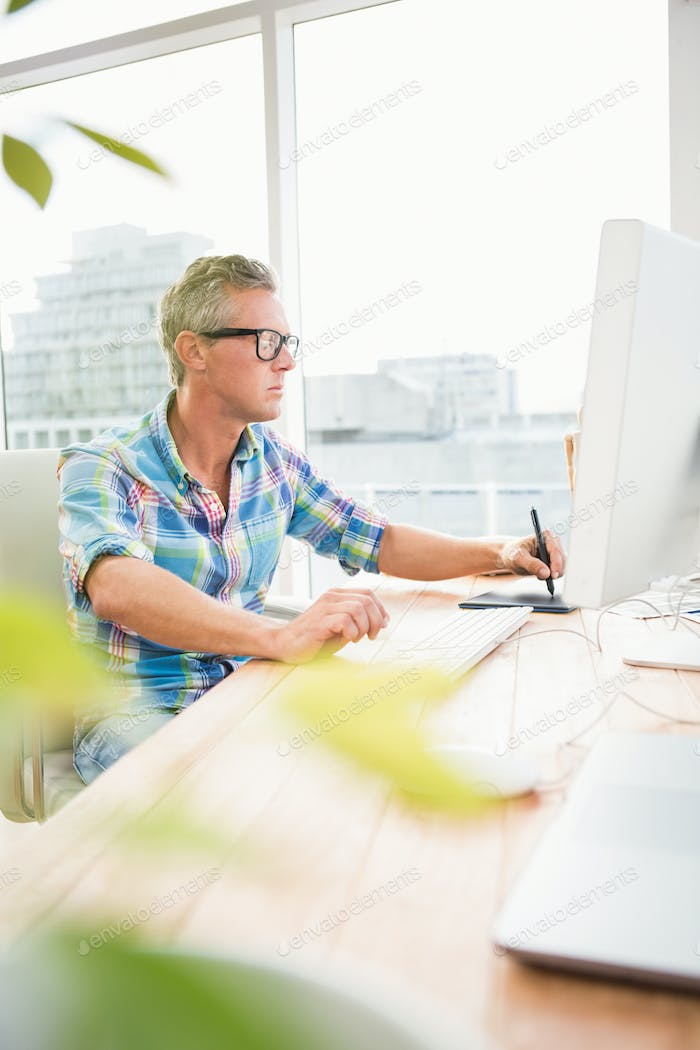 Casual designer using computer and digitizer in the office