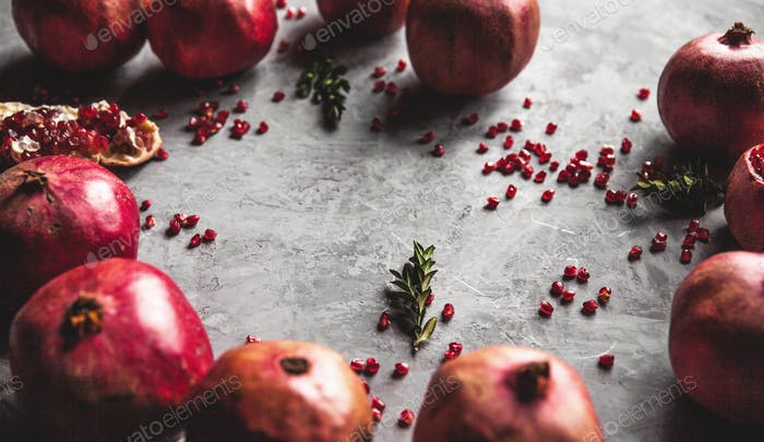 Pomegranate fruit. Ripe and juicy pomegranate on rustic grey background with copy space for your