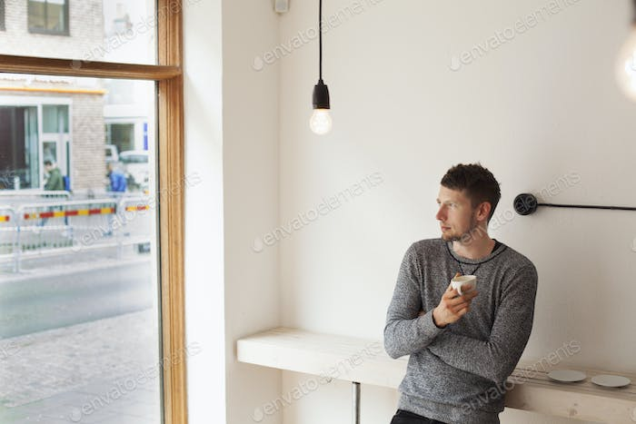 Thoughtful man holding coffee cup while leaning on counter in coffee shop
