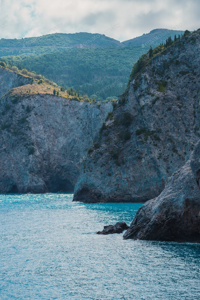 Steep rocky sea shore with cypresses on the plateau. Mediterranean sea