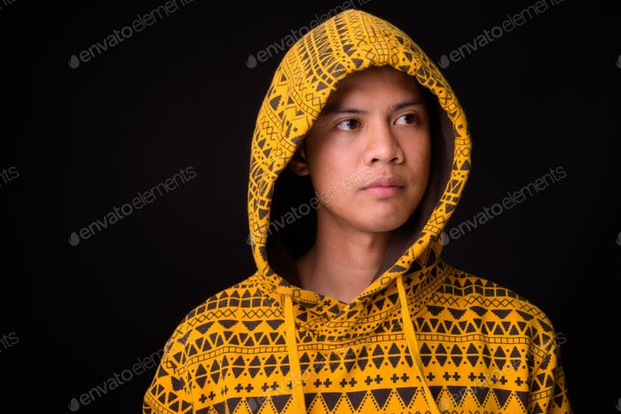 Young Asian man against black background