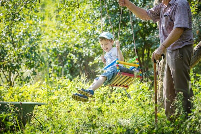 Senior man pushing cheerful grandson on swing