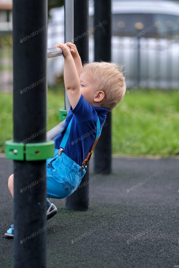 Kleinkind Junge auf dem Spielplatz tragen Shorts und Hosenträger