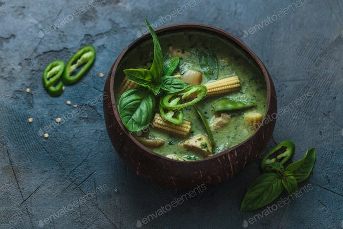 Thai chicken green curry on dark background, copy space