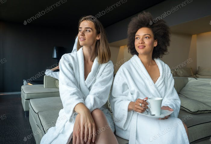 Women in bathrobes enjoying tea and wellness weekend